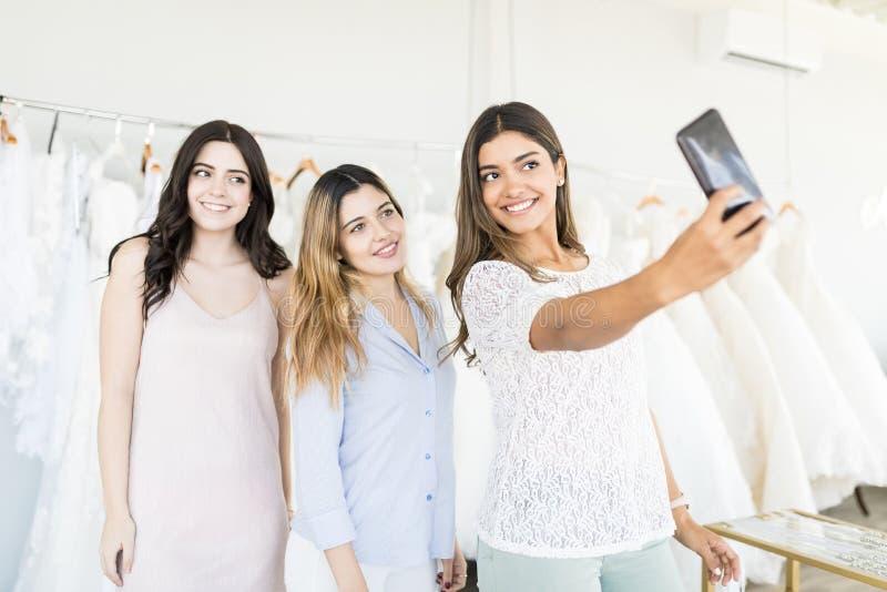 Lächelnde Frauen, die Gedächtnisse des Einkaufens in der Brautboutique gefangennehmen lizenzfreies stockfoto