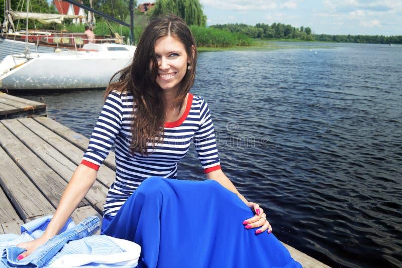 Lächelnde Frauen, die nahe Wasser im Hafen sitzen lizenzfreie stockbilder
