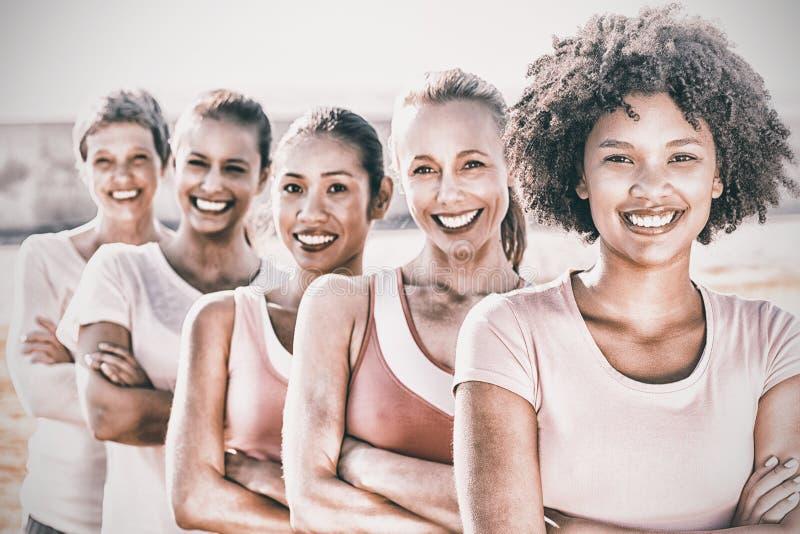 Lächelnde Frauen, die Rosa für Brustkrebs mit den Armen gekreuzt tragen lizenzfreies stockbild