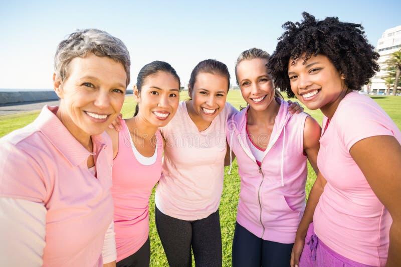 Lächelnde Frauen, die Rosa für Brustkrebs tragen stockfotos