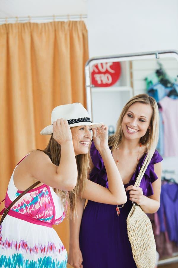 Lächelnde Frauen, die zusammen Kleidung wählen stockfoto