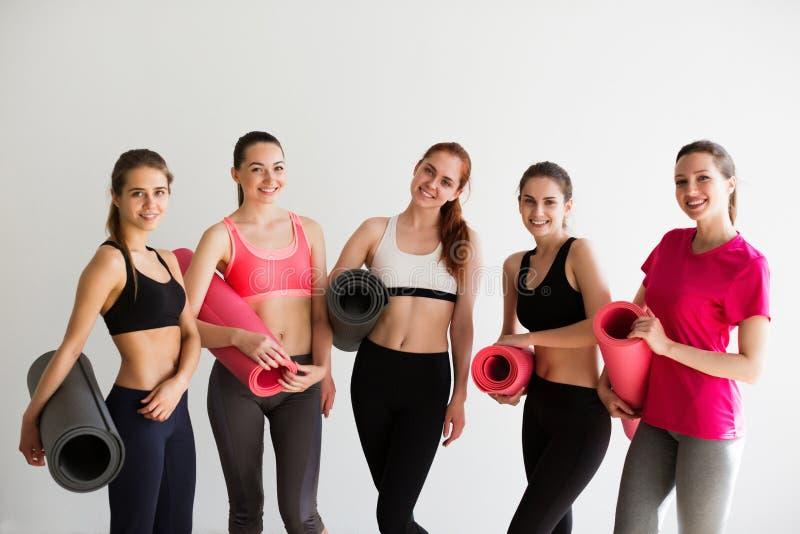 Lächelnde Frauen im Eignungsstudio vor Yoga klassifizieren auf Weiß lizenzfreie stockfotos