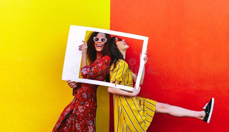 Lächelnde Frauen mit leerem Fotorahmen lizenzfreie stockbilder