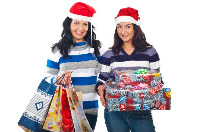 Lächelnde Frauen mit Sankt-Hüten und Weihnachtsgeschenken lizenzfreie stockbilder