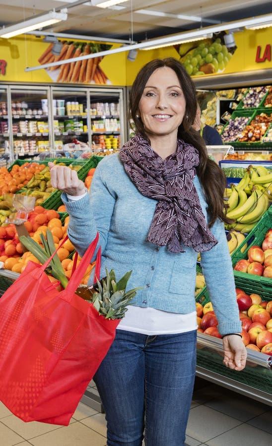 Lächelnde Frauen-tragende Einkaufstasche im Frucht-Speicher stockfoto