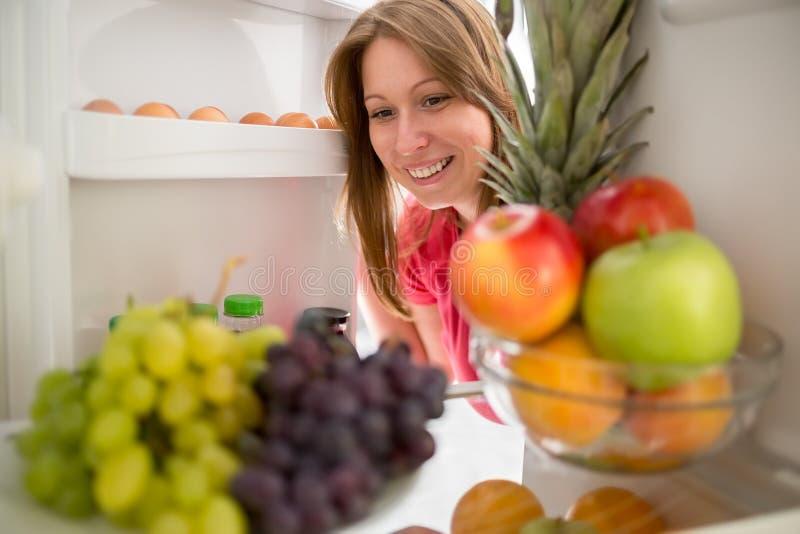Lächelnde Frauenblickfrucht im Kühlschrank lizenzfreies stockbild