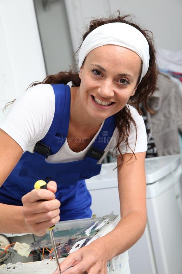 Lächelnde Frauenfestlegungwaschmaschine lizenzfreies stockbild