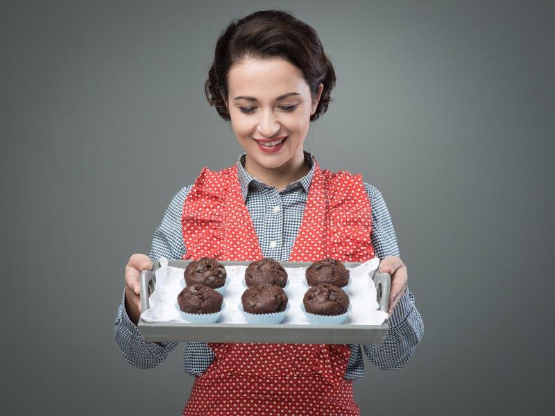 Lächelnde Frauenumhüllungs-Schokoladenmuffins lizenzfreies stockfoto