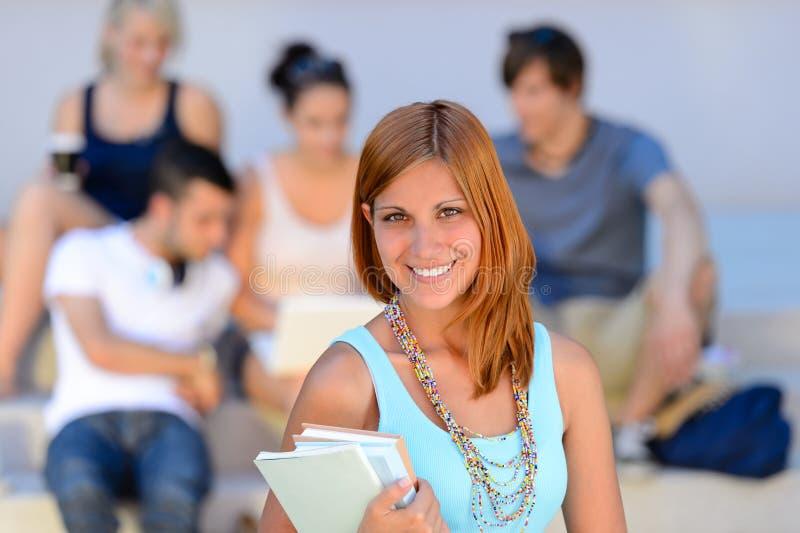 Lächelnde Freunde des SommerStudent-Mädchens hinten stockbild