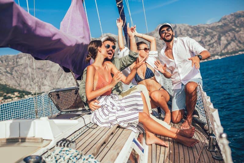 Lächelnde Freunde, die auf Segelbootplattform und -c$haben des Spaßes sitzen lizenzfreies stockbild