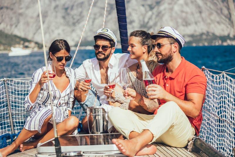 Lächelnde Freunde, die auf Segelbootplattform und -c$haben des Spaßes sitzen stockbild