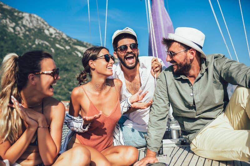Lächelnde Freunde, die auf Segelbootplattform und -c$haben des Spaßes sitzen lizenzfreie stockbilder