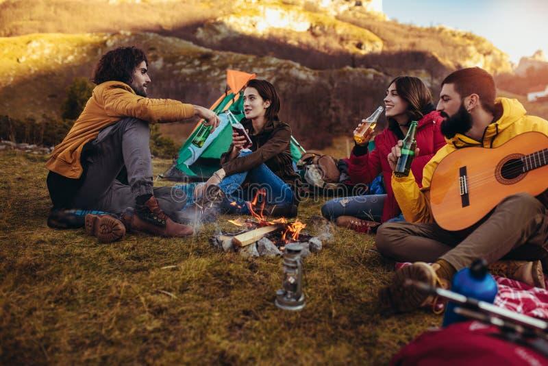 Lächelnde Freunde, die um Feuer beim Kampieren sitzen stockbild