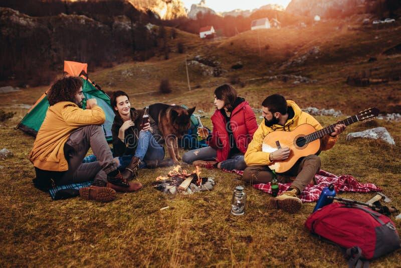 Lächelnde Freunde, die um Feuer beim Kampieren sitzen lizenzfreie stockfotografie