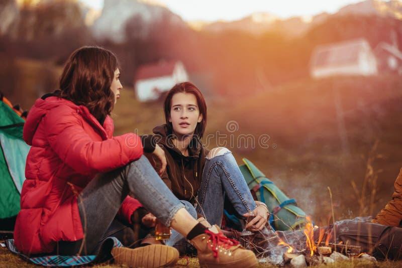 Lächelnde Freunde, die um Feuer beim Kampieren sitzen lizenzfreie stockfotos