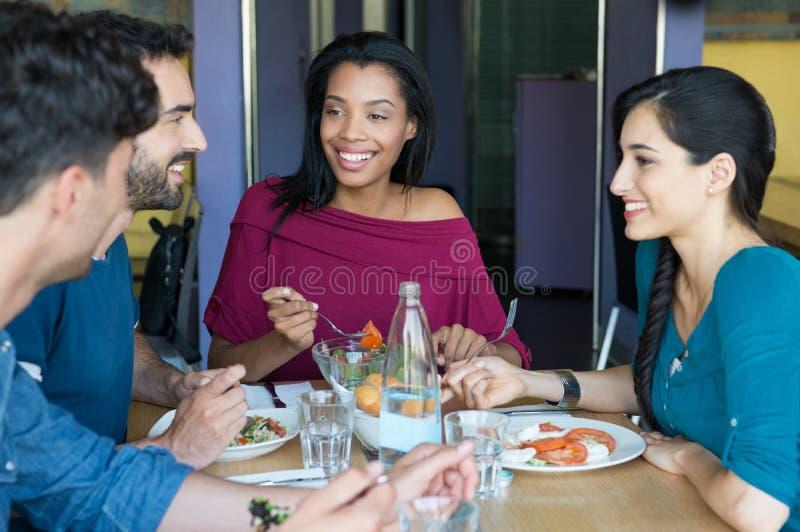 Lächelnde Freunde, die zusammen essen stockbild