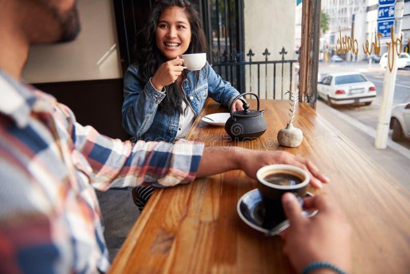 Lächelnde Freunde, die zusammen Kaffee und Tee in einem Café trinken stockbilder