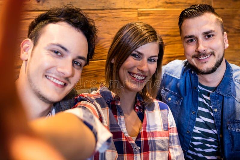 Lächelnde Freunde am Restaurant stockfoto