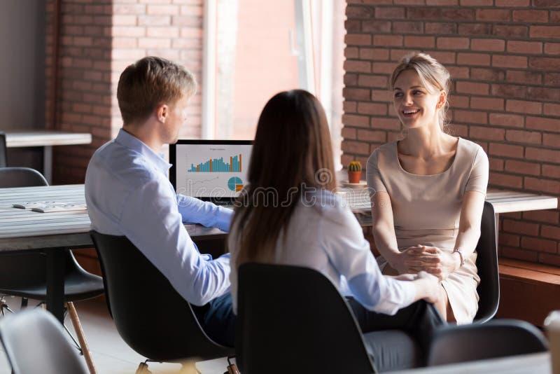 Lächelnde freundliche Geschäftsleute, die Ideen während O teilend plaudern stockfoto