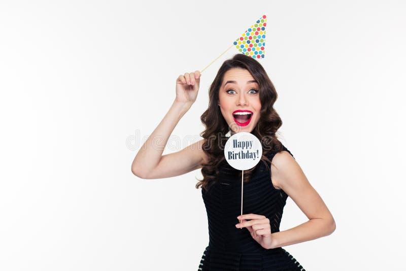 Lächelnde frohe recht gelockte Frau, die mit den Geburtstagsstützen lokalisiert aufwirft stockfotografie