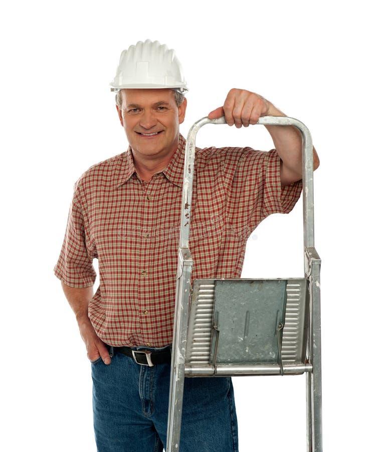 Lächelnde gealterte Arbeitskraft, die mit Strichleiter aufwirft stockfotos