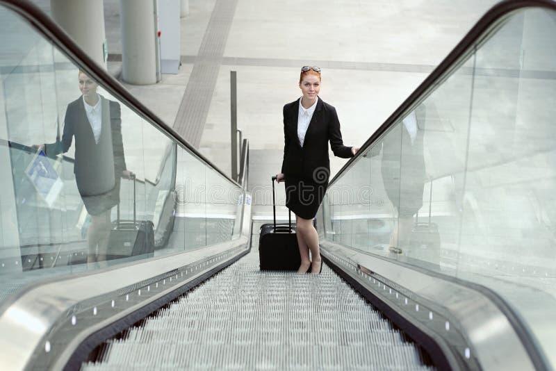 Lächelnde Geschäftsfrau auf Rolltreppe stockbilder