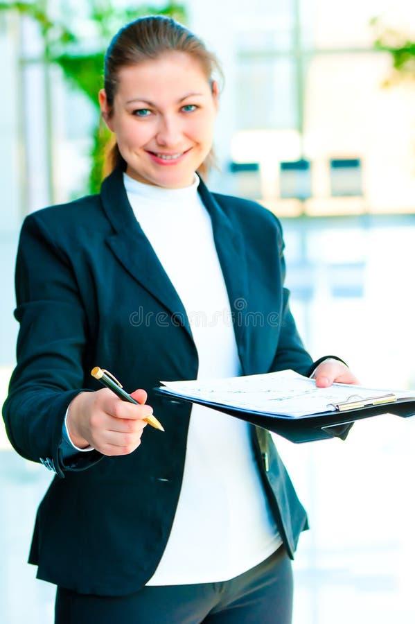 Lächelnde Geschäftsfrau bietet an, das Dokument zu unterzeichnen lizenzfreie stockfotos