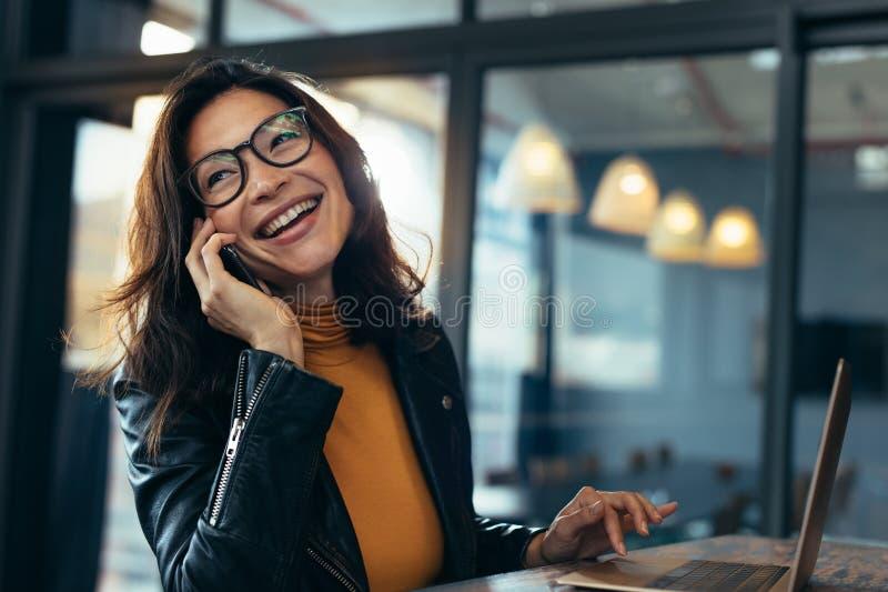 Lächelnde Geschäftsfrau in der zufälligen Unterhaltung am Telefon stockfoto