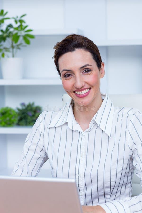 Lächelnde Geschäftsfrau des hübschen Brunette, die Laptop verwendet stockfotos