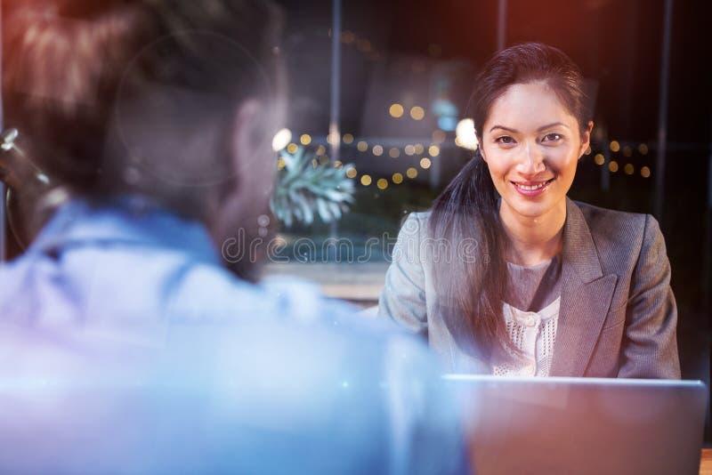 Lächelnde Geschäftsfrau, die auf Kollegen einwirkt lizenzfreies stockbild