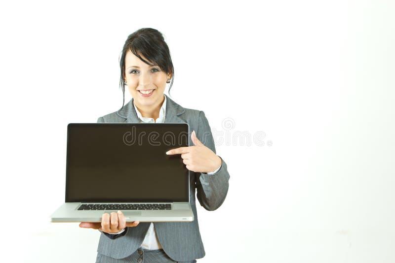 Lächelnde Geschäftsfrau, die auf Laptop zeigt stockfotos