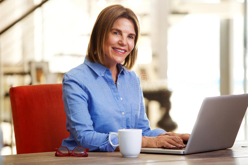 Lächelnde Geschäftsfrau, die bei Tisch mit Laptop sitzt stockfoto