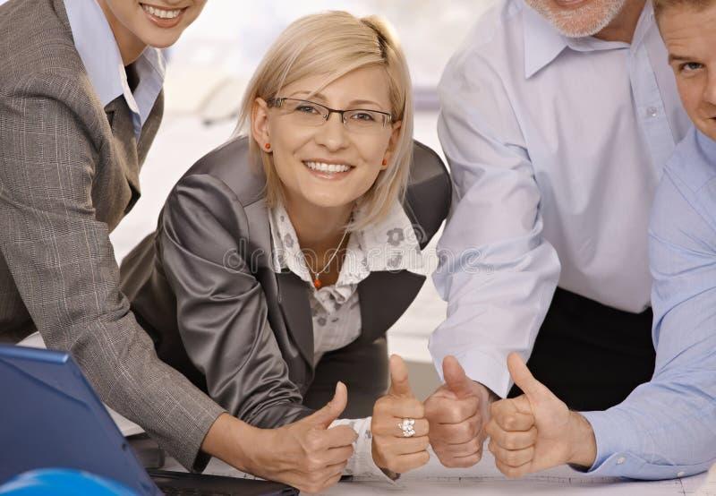 Lächelnde Geschäftsfrau, die Daumen mit Team aufgibt lizenzfreie stockfotos
