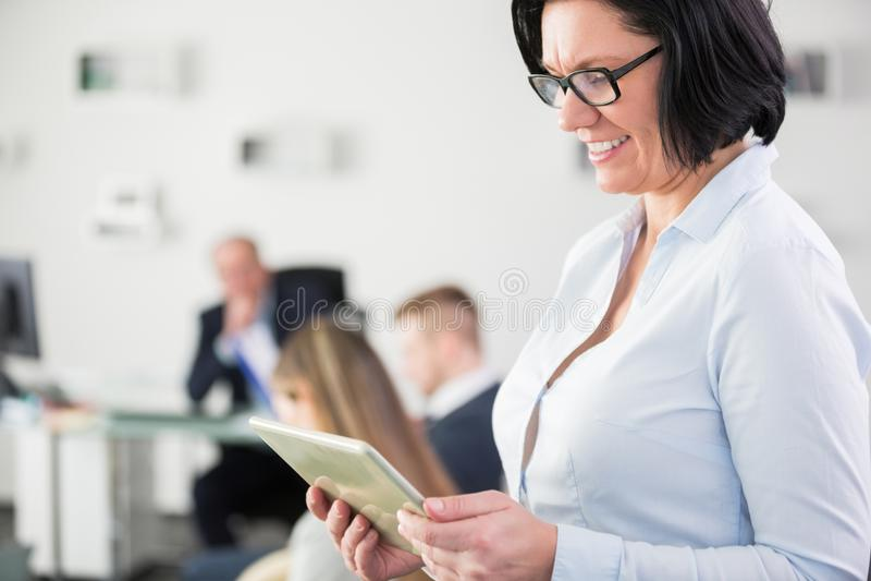 Lächelnde Geschäftsfrau, die digitale Tablette im Büro verwendet lizenzfreies stockfoto