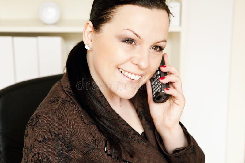 Lächelnde Geschäftsfrau, die durch Telefon benennt stockfotografie
