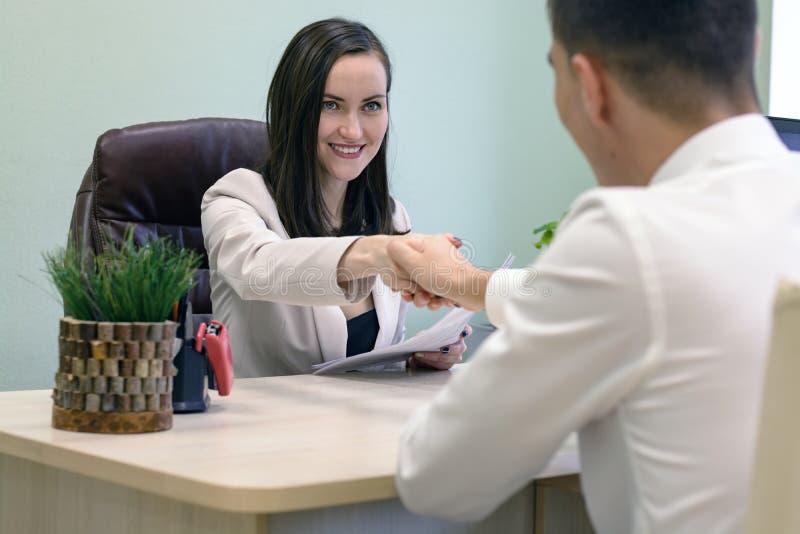 Lächelnde Geschäftsfrau, die Hände mit einem jungen Geschäftsmann am Schreibtisch im Büro rüttelt Das Konzept des Interviews, Ver stockbilder