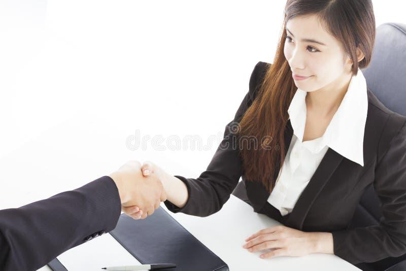 Lächelnde Geschäftsfrau, die Hände mit Kunden rüttelt lizenzfreies stockfoto