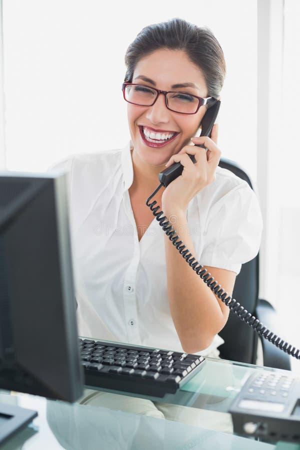 Lächelnde Geschäftsfrau, die an ihrem Schreibtisch spricht am Telefon sitzt lizenzfreies stockbild