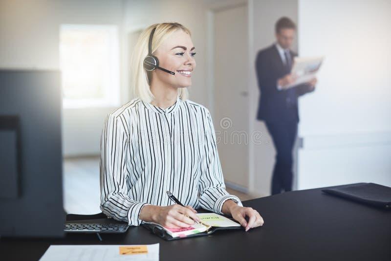 Lächelnde Geschäftsfrau, die ihren Tagesplaner in einem Büro überprüft stockbild