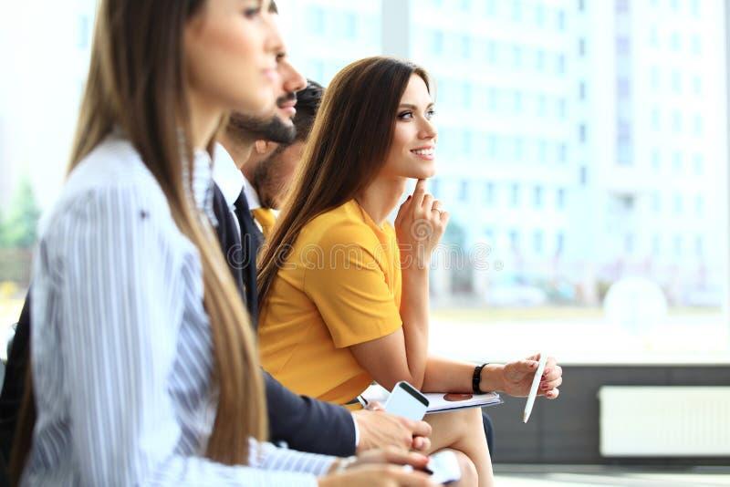 Lächelnde Geschäftsfrau, die Kamera auf Seminar betrachtet lizenzfreie stockfotos