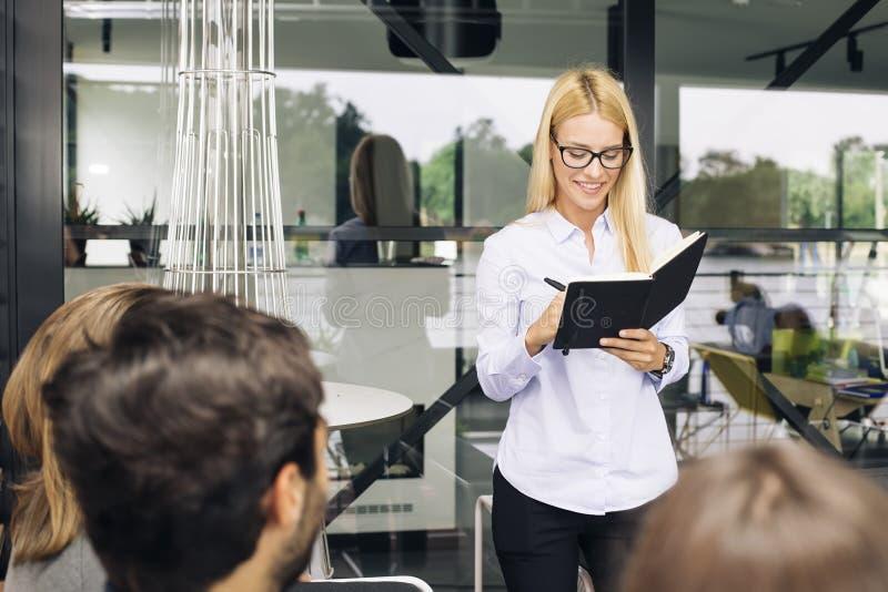 Lächelnde Geschäftsfrau, die mit ihrem Kollegen im hellen Büro spricht lizenzfreies stockbild