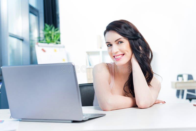 Lächelnde Geschäftsfrau, die mit Laptop-Computer im Büro arbeitet lizenzfreie stockbilder