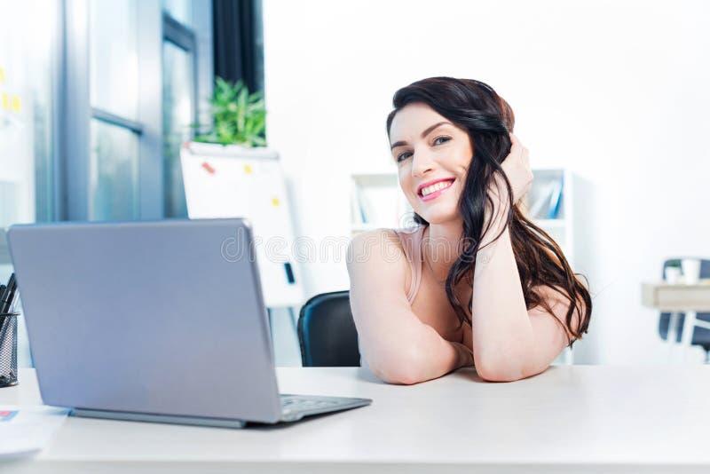 Lächelnde Geschäftsfrau, die mit Laptop-Computer im Büro arbeitet stockfotografie