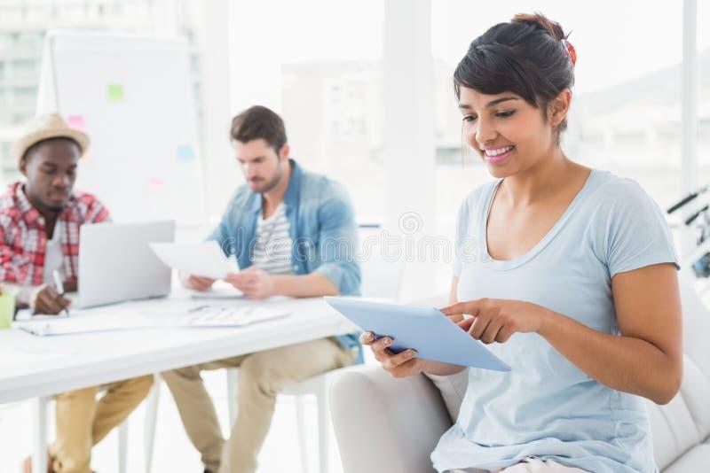 Lächelnde Geschäftsfrau, die Tablette auf Couch verwendet stockbild