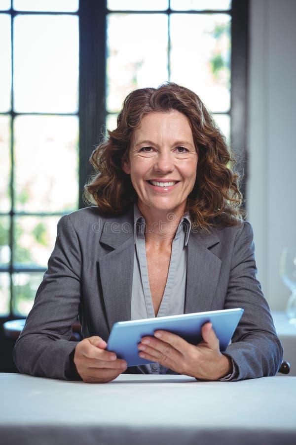 Lächelnde Geschäftsfrau, die Tablette verwendet lizenzfreie stockfotos