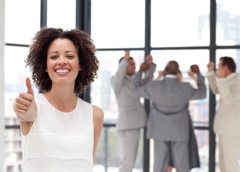 Lächelnde Geschäftsfrau, die Teamspiritus zeigt stockfotografie