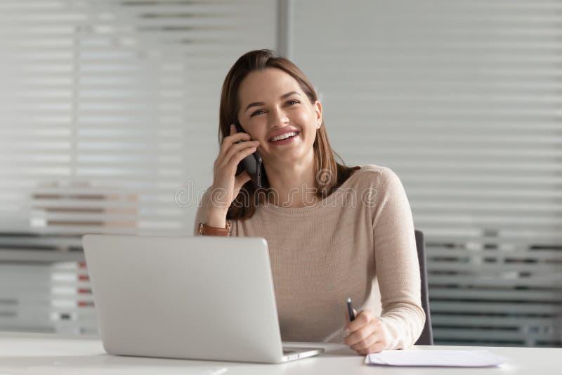 Lächelnde Geschäftsfrau, die am Telefon macht Geschäftsanruf bei der Arbeit spricht lizenzfreies stockfoto