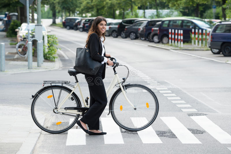 Lächelnde Geschäftsfrau With Handbag Commuting auf Fahrrad stockfotografie