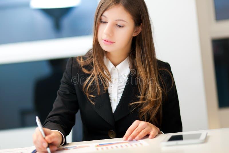 Lächelnde Geschäftsfrau im Büro lizenzfreie stockbilder