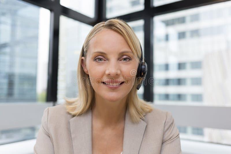 Lächelnde Geschäftsfrau im Büro auf Videokonferenz, Kopfhörer lizenzfreie stockfotos